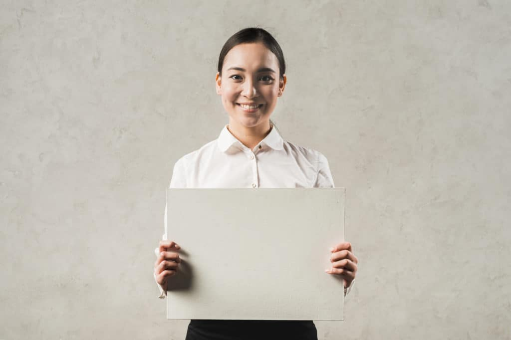 Smiling Businesswoman Holding Blank Name Placard